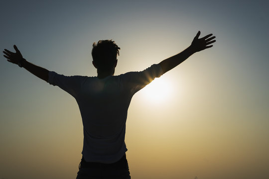Silhouette of a happy man is strong confidence open arms under the sunset om the top. Freedom and victory concept.