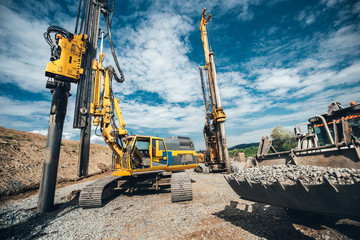 Highway construction site with heavy duty machinery. Two Rotary drills, bulldozer and excavator working Wall mural