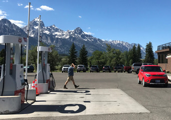 A man walks past gas pumps in front of Dornans Trading Post and Deli, with the Rocky Mountains Teton Range in the background