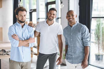 multiethnic young businessmen looking at camera while standing in office