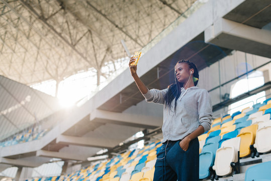 The beautiful afro-american girl is taking selfie via the mobile phone at the backgroud of the seat of the stadium. The sunlits.