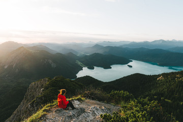 Woman in red jacket looking over a valley with mountains, forest and lake in Germany in the morning