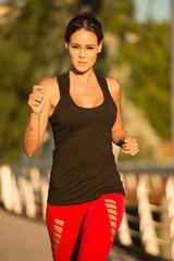 Beautiful woman running over bridge in the morning