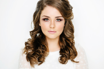 Young beautiful brunette with curls on a white background. The girl with a gentle makeup and stylish hair