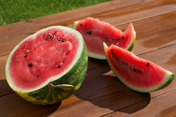 Slices of watermelon on a wooden table in the garden