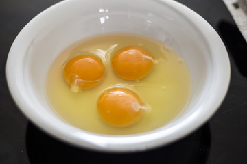 Eggs in white bowl close up top view