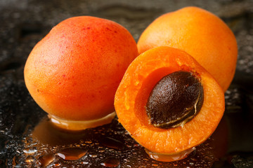 Close up of two and a half sliced apricot fruits with the stone, freshly washed with water drops on a dark background
