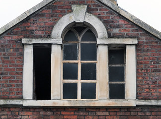 broken windows in an abandoned derelict old commerical building with brickwork stone frame and roof, Halifax england