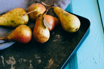 Fresh homemade pears on an old black baking sheet, blue background