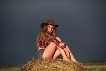 Young woman in shorts and cowboy hat sitting on a haymow