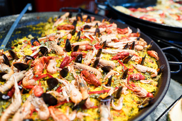 Large skillet with paella, yellow rice, mussels and seafood
