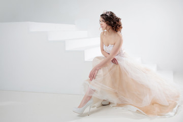 Bride sits on the stairs. Portrait of a beautiful girl in a wedding dress. Dancing Bride, white background.