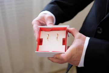 Box with wedding rings in hands of the groom