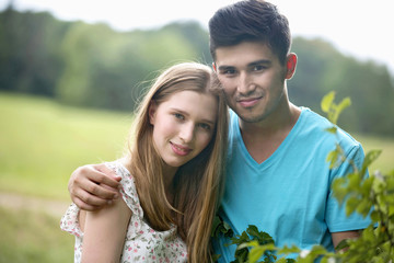 Portrait Of Romantic Young Couple Standing In Summer Field
