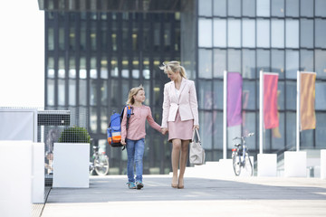 Mother Walking Daughter To School In Urban Setting