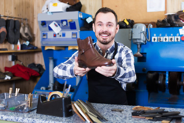 Happy male worker showing fixed shoes