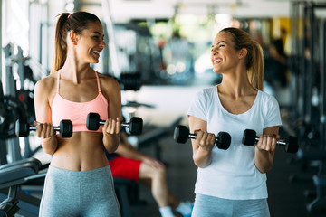 Beautiful women doing exercises in gym together