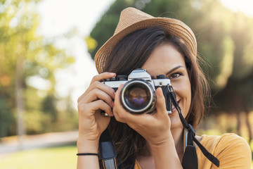 Smiling young woman using a camera to take photo.