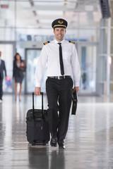 Portrait Of Airline Pilot Walking Through Airport Lounge