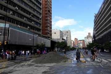 People walk past a pile of sand used by protesters to block a street during a protest against Venezuelan President Nicolas Maduro's government in Caracas