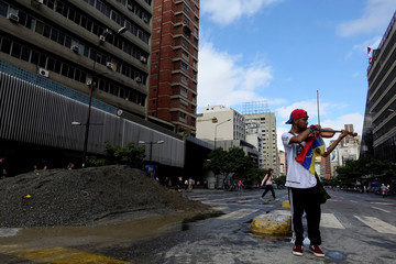 Venezuelan violinist Wuilly Arteaga plays the violin next to a pile of sand used by protesters to block the street during a protest against Venezuelan President Nicolas Maduro's government in Caracas