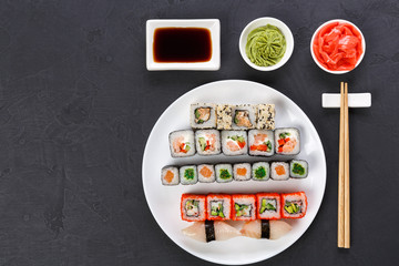 Set of sushi and rolls on gray background, top view