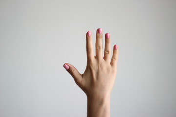 Young woman's hand with pink manicure. Gesture.