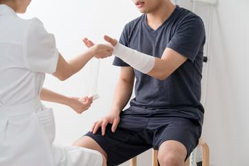 腕に包帯を巻く看護師、患者