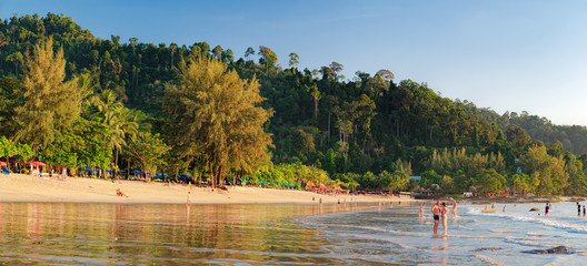 Tourists have a rest, walk and watch the colorful sunset at Nang Thong Beach, Andaman Sea, Khao Lak, Thailand. Relaxing on paradise beach with palms trees