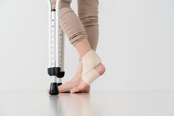 サポーターを巻いた女性、松葉杖