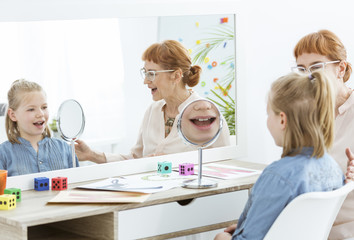 Speech therapist using mirror exercises