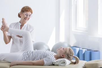 Physiotherapist massaging little girl's leg