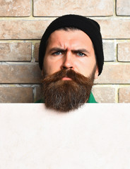 Bearded brutal caucasian hipster with white paper sheet