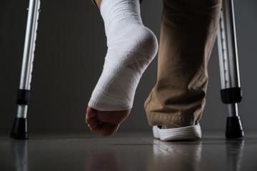 足を怪我した男、松葉杖