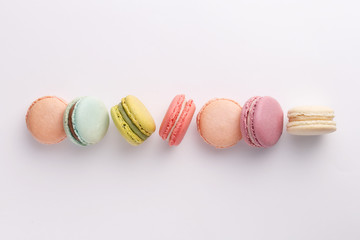 Macarons on white background. Colorful french desserts. Top view