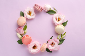 Foto op Textielframe Macarons Macarons and flowers wreath on a purple background. Colorful french dessert with fresh flowers. Top view