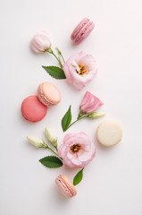 Macarons, coffee and flowers on a white background. Colorful french dessert with fresh flowers. Top view