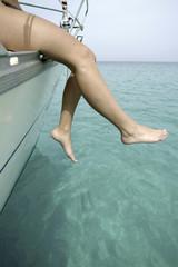 Junge Frau mit baumelnden Beinen auf einer Segelyacht - AS
