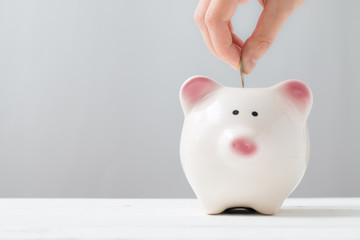 Inserting a coin into a piggy bank. Minimal style. Money savings concept.