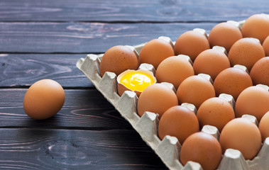 Top view of chicken eggs in a cardboard box on a dark wooden table with copy space.