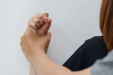 Man hand oppressing or pressing woman wrist on the wall - woman violence concept.