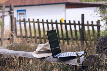 Laptop on a wooden board outdoors