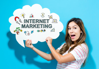 Internet Marketing text with young woman holding a speech bubble on a blue background