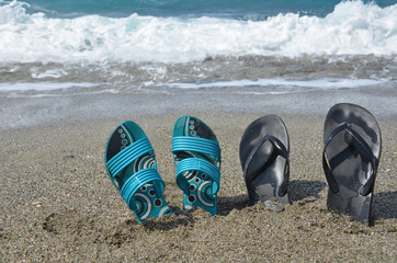 Two pairs of flip-flops on the beach, tropical vacation concept