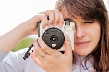 Lovely young long-haired girl with instant camera.