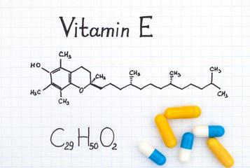 Chemical formula of Vitamin E and pills.