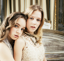 two pretty twin sister blond curly hairstyle girl in luxury house interior together, rich young people concept