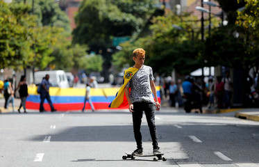 A man wearing the Venezuelan national flag over his shoulders rides a skateboard at an avenue blockade during a rally against Venezuelan President Nicolas Maduro's government in Caracas
