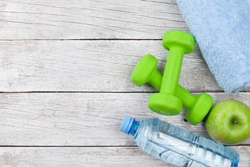Fitness concept. Dumbbells, apple and water