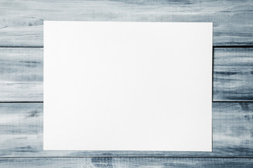 Mock up of blank paper sheet over wooden background